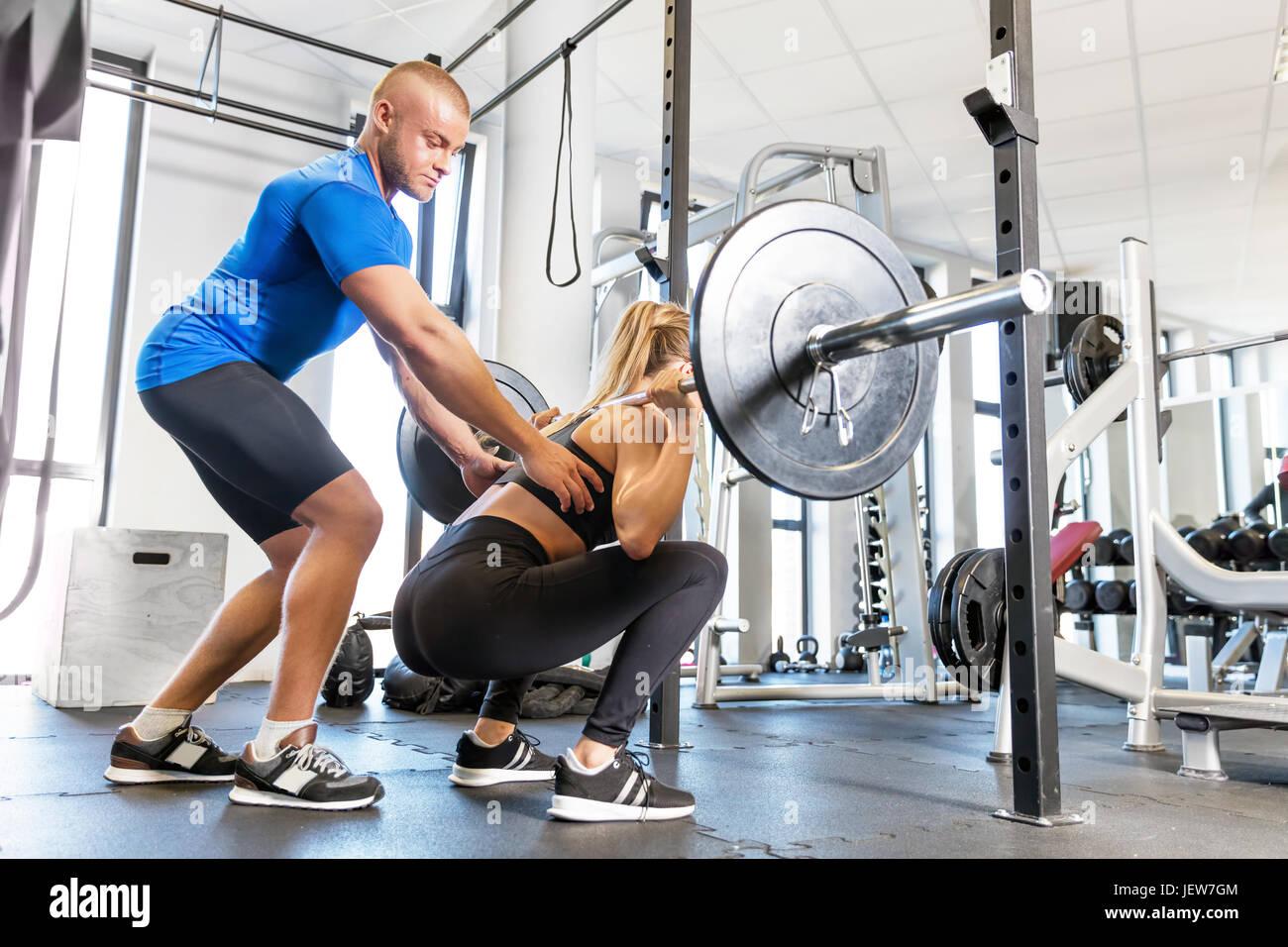 Entrenador personal trabajando con un cliente en el gimnasio. La Halterofilia workout asistencia y motivación. Concepto de deporte. Foto de stock