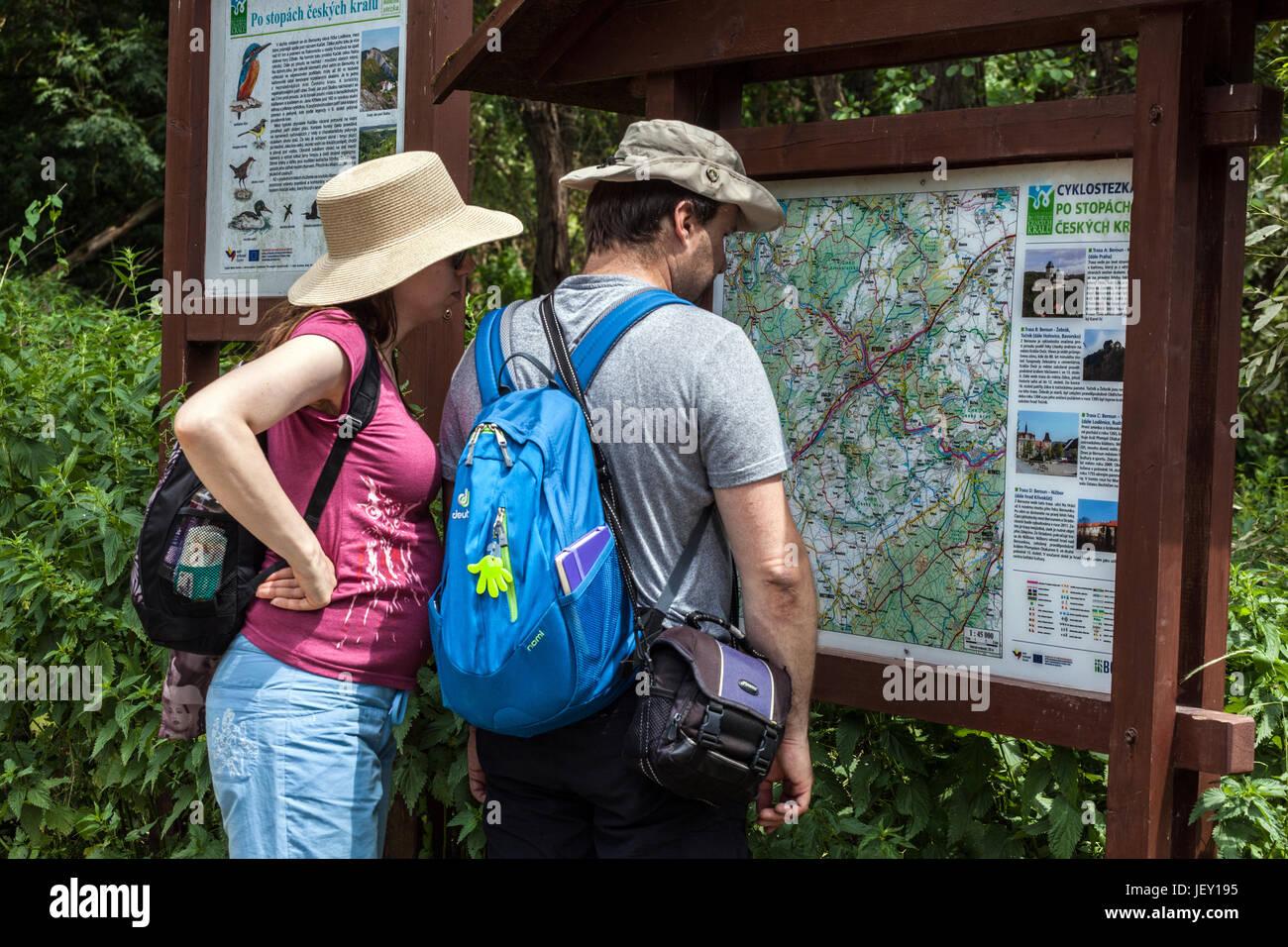 Pareja en un viaje en el valle del río Berounka, mirando en el tablón de información con un mapa Imagen De Stock