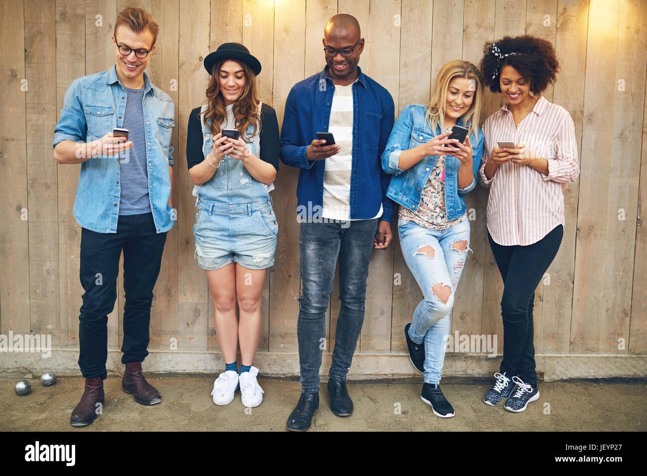 Alegre grupo de amigos en blanco y negro de pie y mostrando sus smartphones juntos en la pared de madera. Imagen De Stock