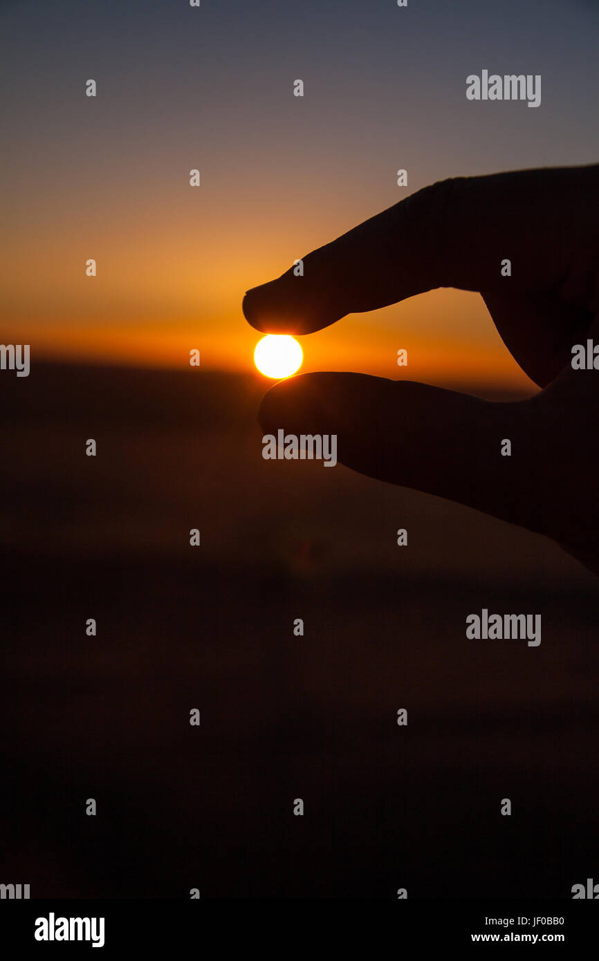 Silueta de la Mano agarrando el sol Imagen De Stock