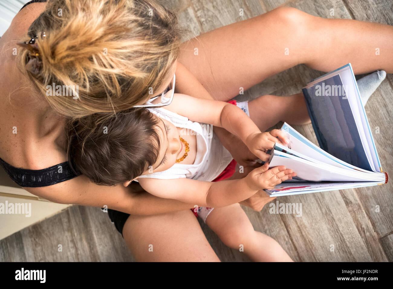 Mamá leer historias a los niños libro de navegación Imagen De Stock