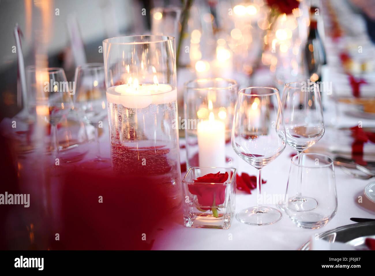 Una cena romántica con velas mesa con elegante cristalería y flores rojas sobre un mantel blanco en una vista de Foto de stock
