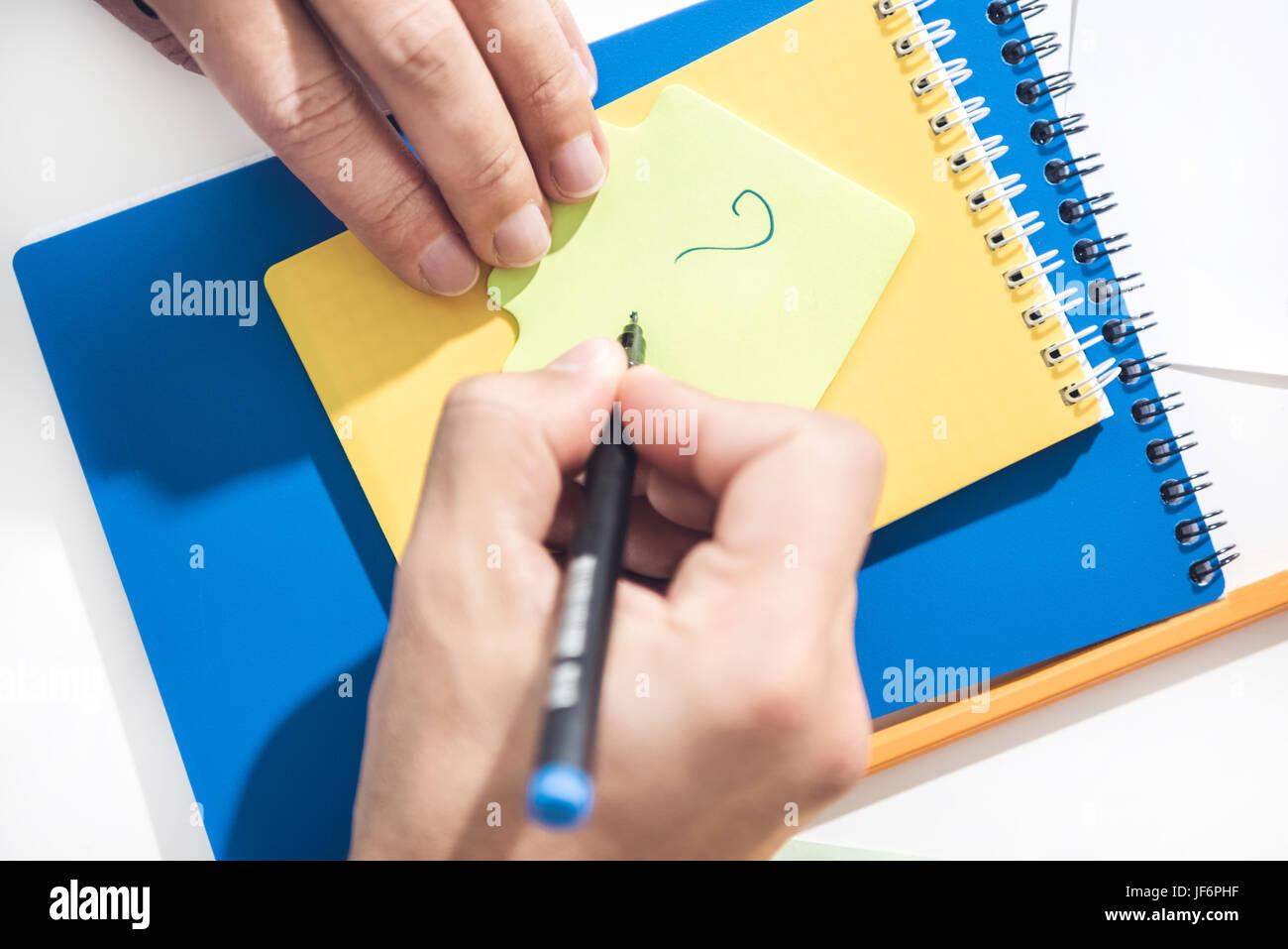 Cerca de manos humanas exclamación de dibujo en una nota con el lápiz, el establecimiento de empresas Imagen De Stock