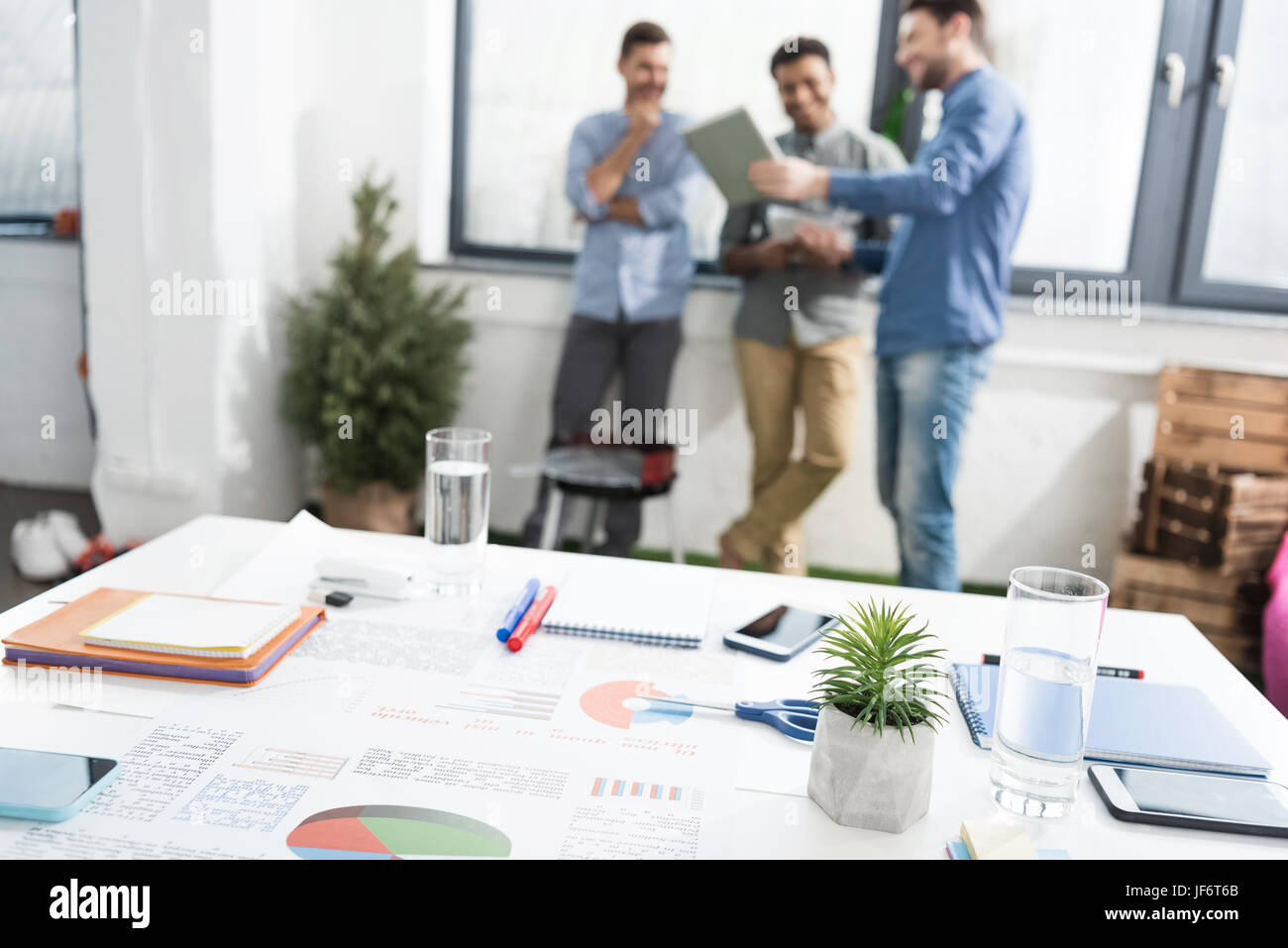 Vista cercana de gráficos de negocios y suministros de oficina en el escritorio y empresarios de pie detrás, Imagen De Stock