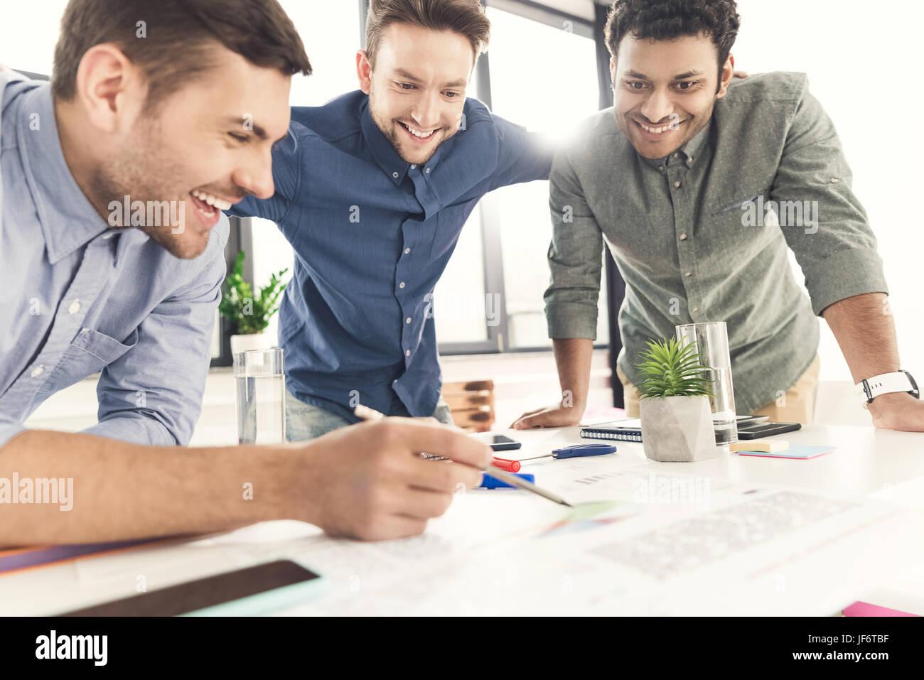 Tres jóvenes empresarios apoyándose en la mesa y trabajar en el proyecto juntos, el concepto de trabajo Imagen De Stock