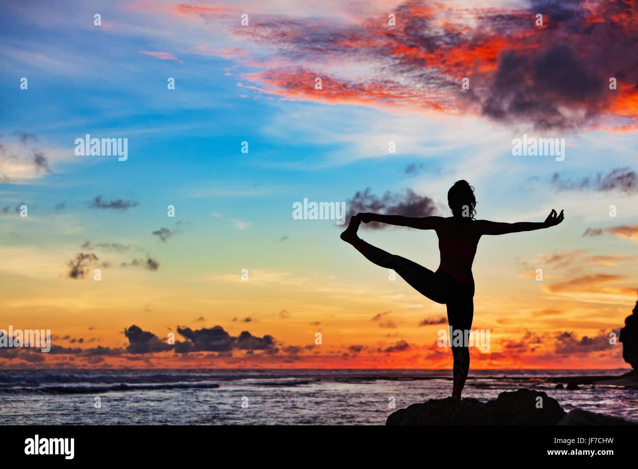 Meditación al atardecer silueta. Mujer activa de pie en pose de yoga en la playa rock salud para mantenerse Imagen De Stock