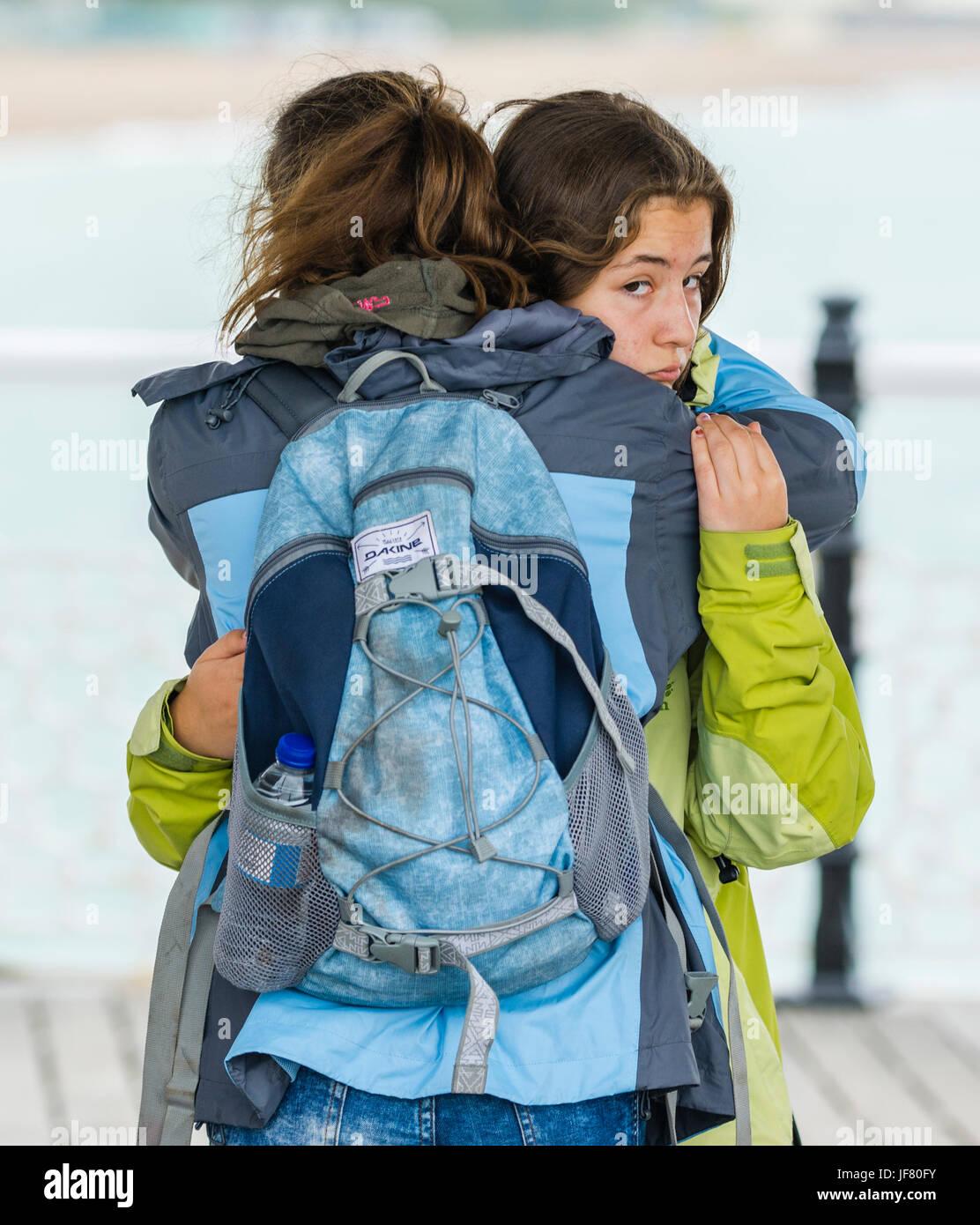 Las niñas abrazarse. Las niñas con un abrazo de consuelo como uno de ellos spots el fotógrafo. Imagen De Stock