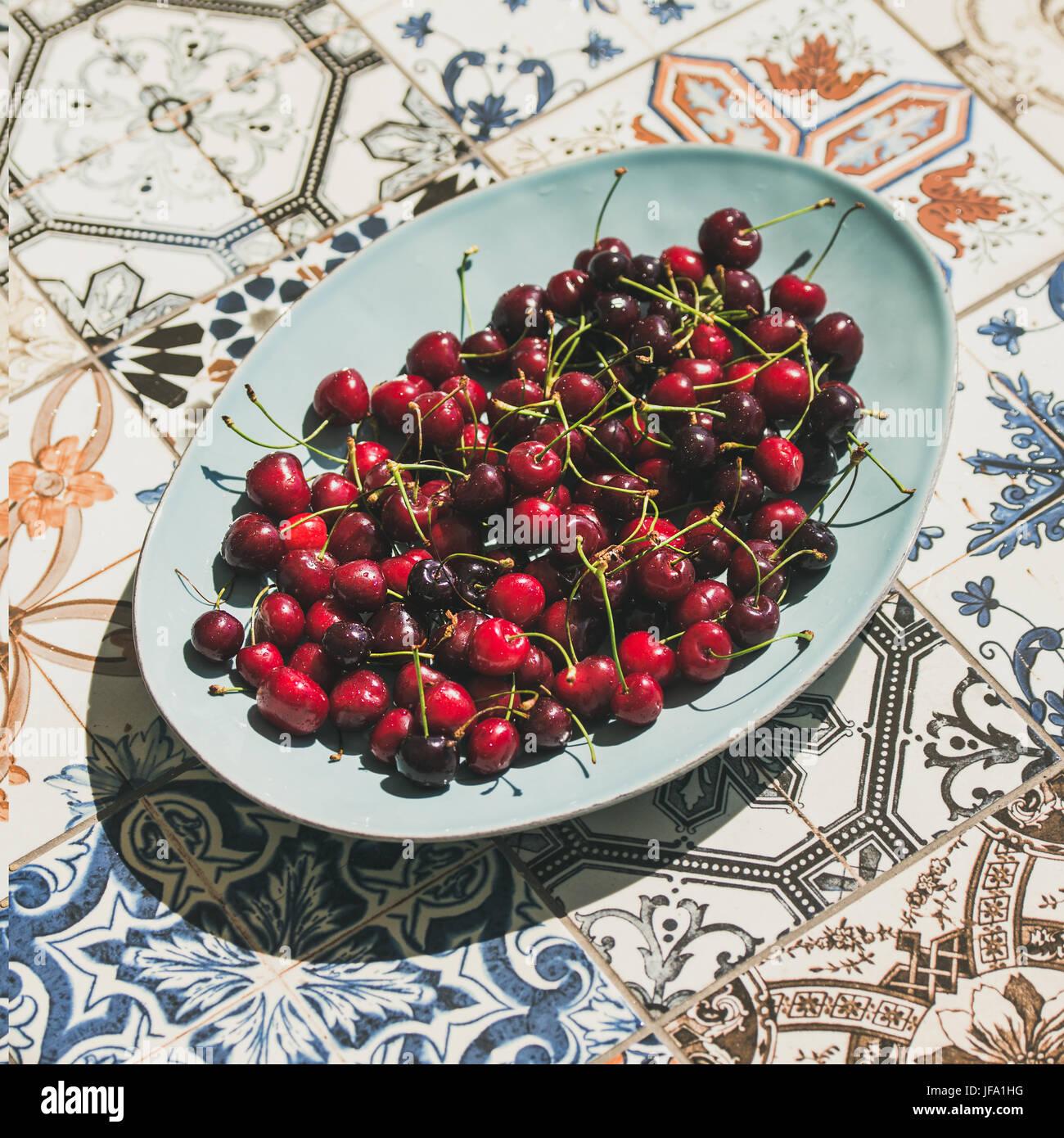 Las cerezas dulces frescas en la placa sobre fondo baldosas cerámicas orientales Imagen De Stock