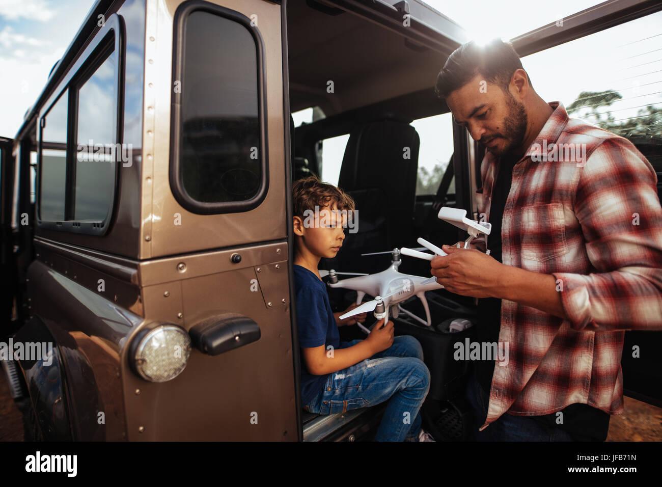 Foto de padre e hijo en la parte de atrás de su coche configurando un avión para volar. Joven e hijo ensamblar Imagen De Stock