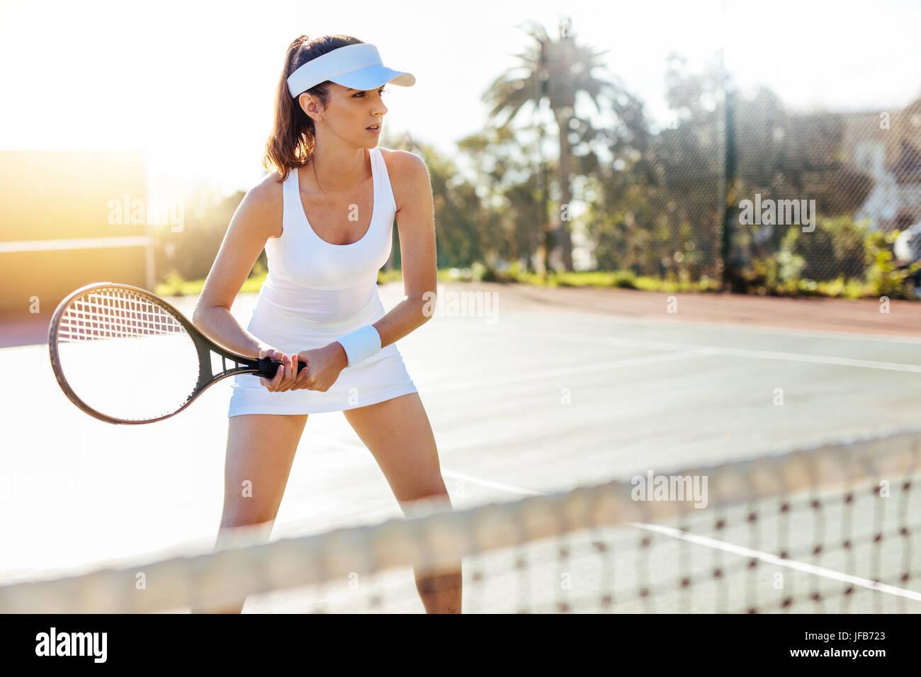 ab8c61a52c Hermosa sportswoman con raqueta en la cancha de tenis. Mujer joven de pie  en una corte al aire libre y jugando un partido de tenis.