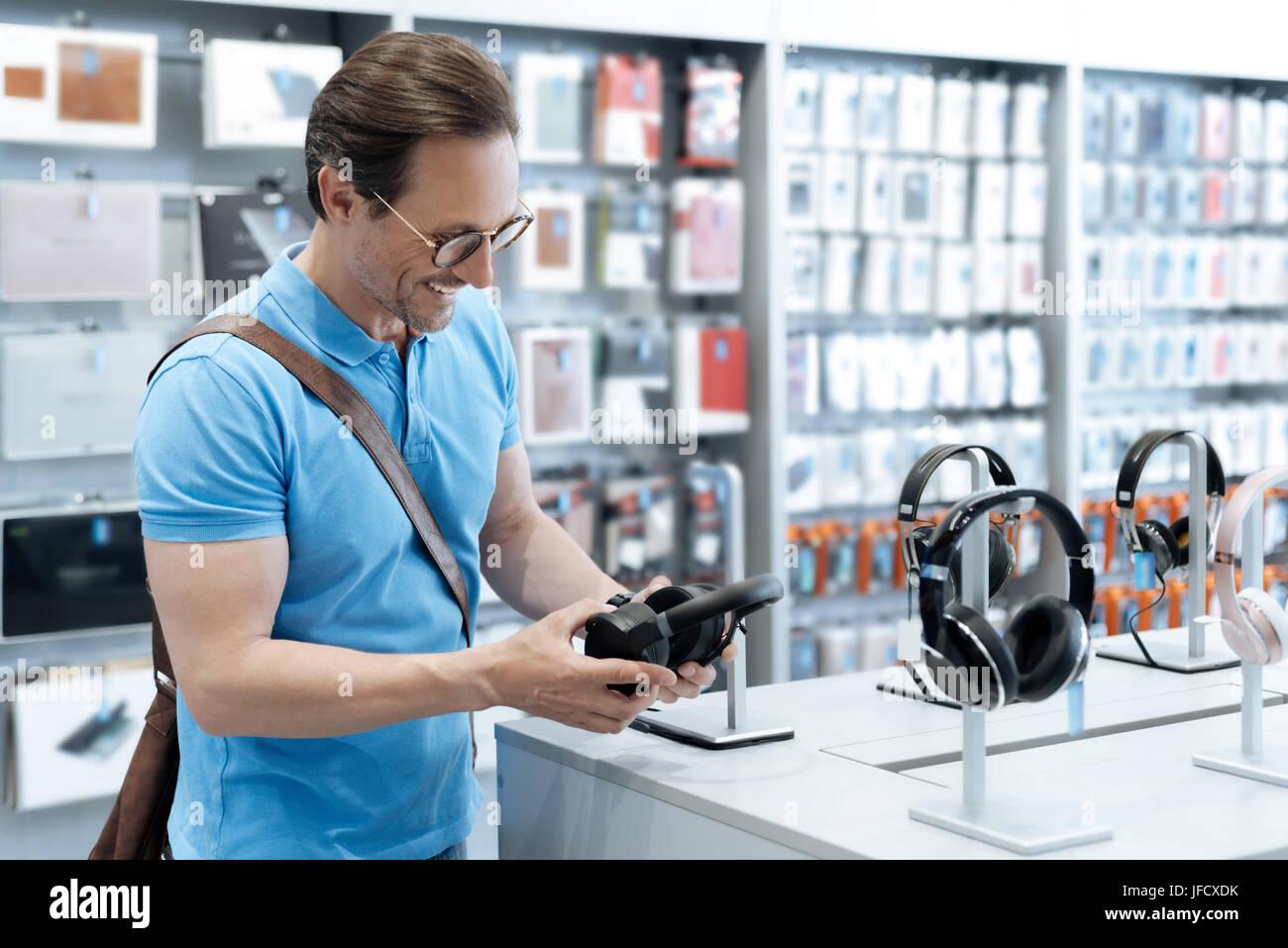Creo que estos son nuevos. Hombre positivo llevar vestimenta casual transmitir mientras está de pie en una Imagen De Stock