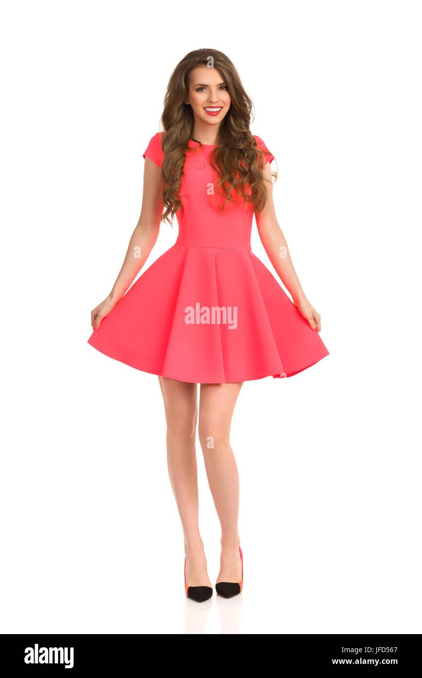75c61c98fc Hermosa joven en rosa mini vestido y tacones altos posando. Vista frontal.  longitud completa