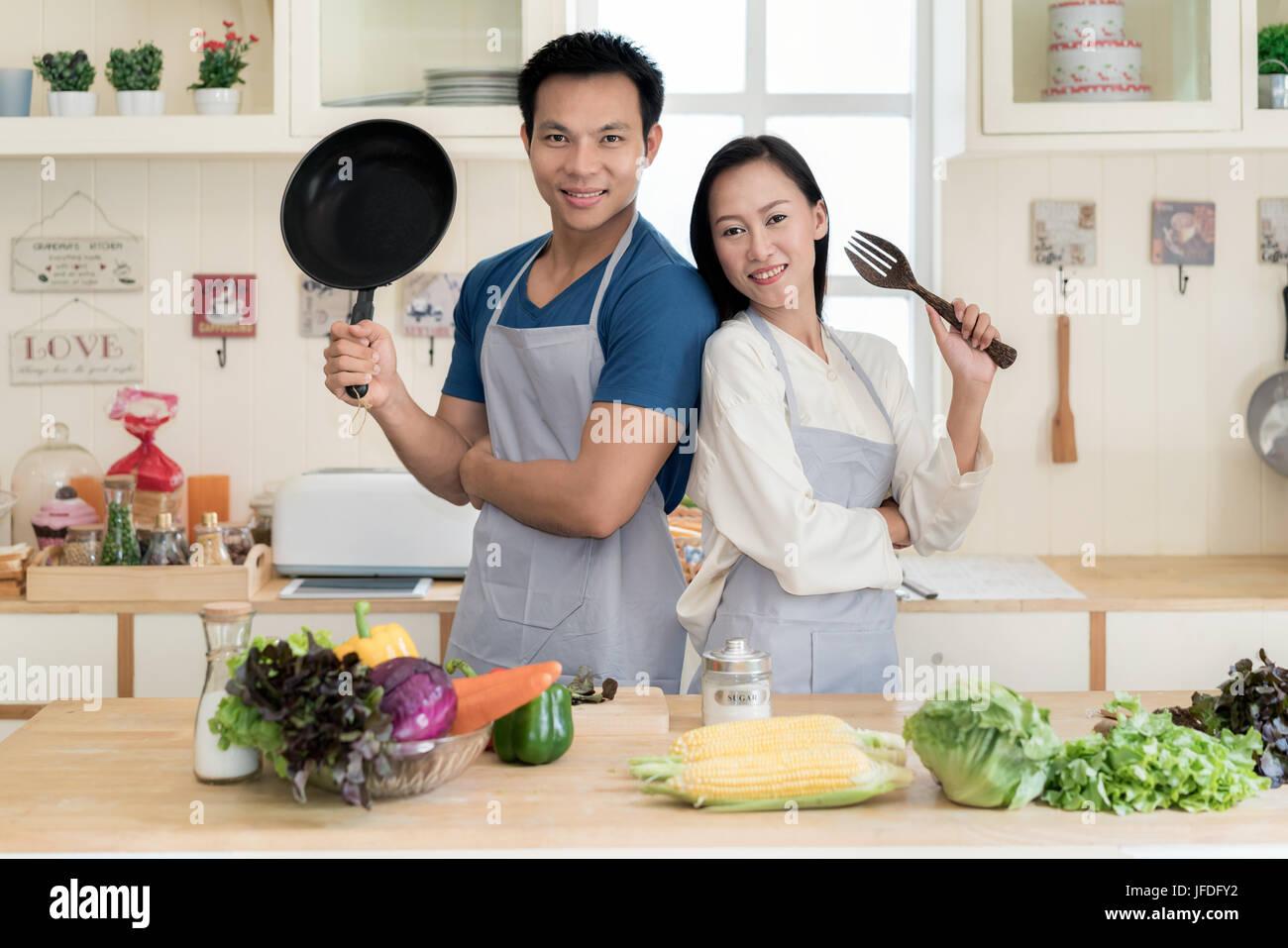 Pareja joven asiático junto al contador preparando la comida en la cocina. Feliz pareja amor concepto. Foto de stock