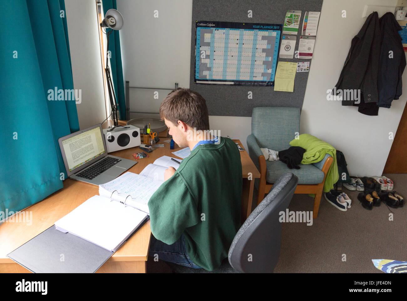 Estudiante en la Universidad de Cambridge estudiando en su habitación en Queens College de la Universidad de Imagen De Stock