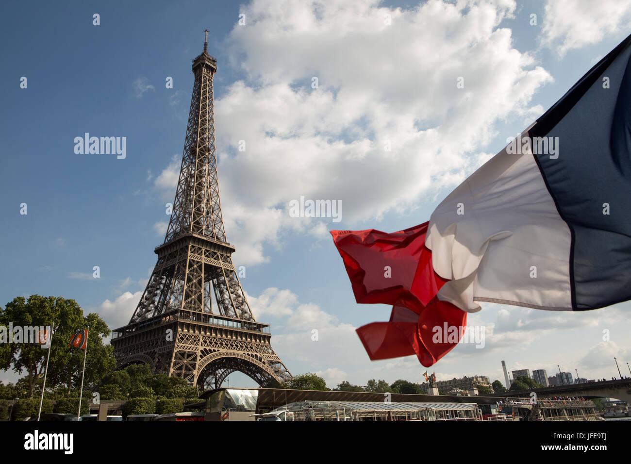 La bandera francesa sopla el viento delante de la Torre Eiffel. Foto de stock