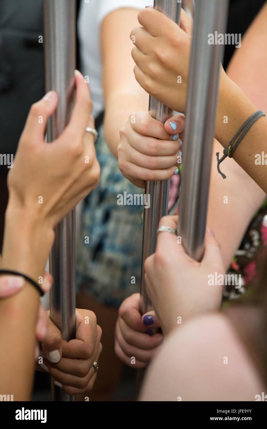 Los viajeros agarrar el asa metálica en el interior de un vagón de metro. Imagen De Stock