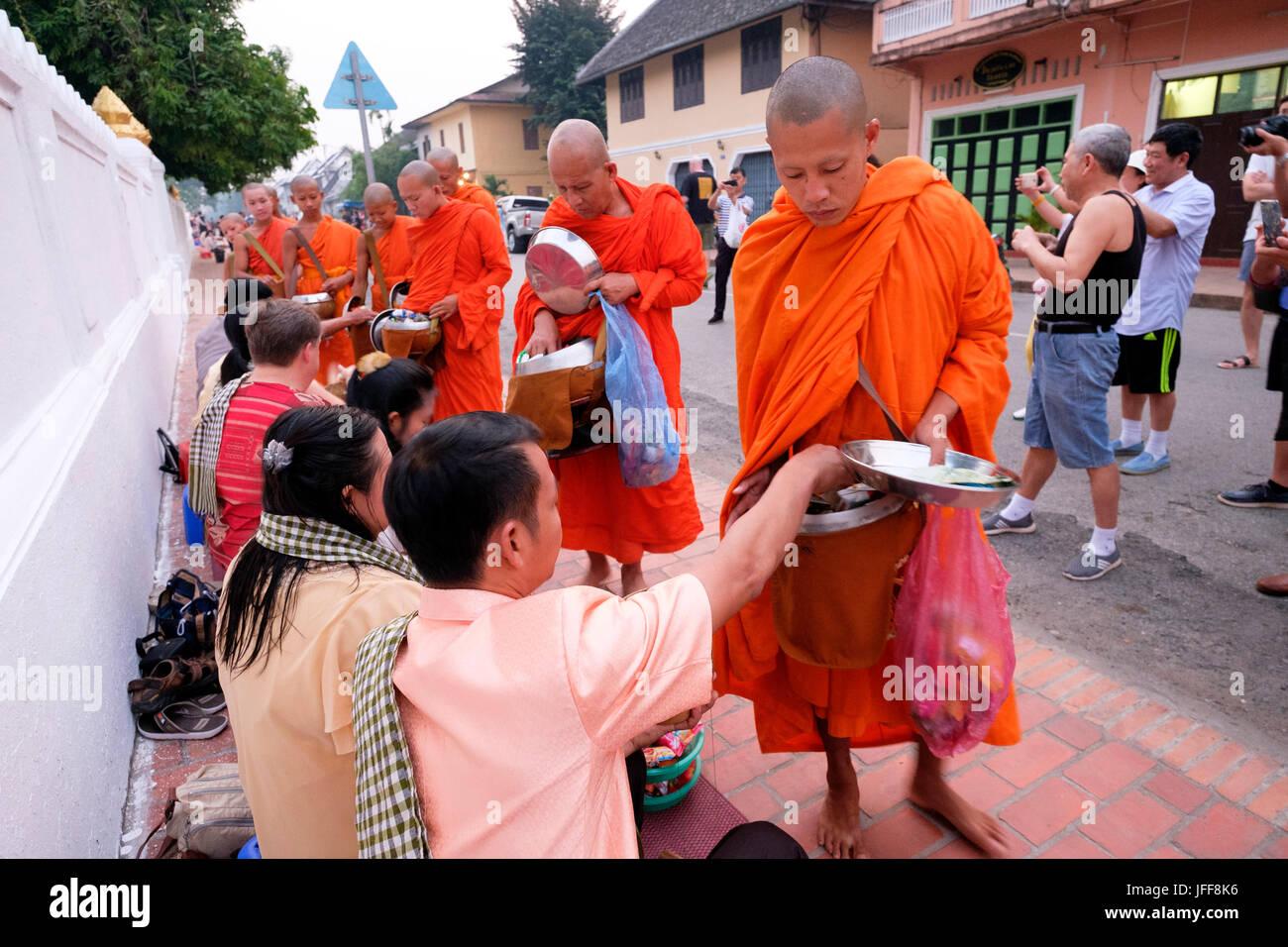 Procesión de monjes budistas vistiendo ropas naranjas al amanecer para recoger regalos en las calles de Luang Prabang, Foto de stock