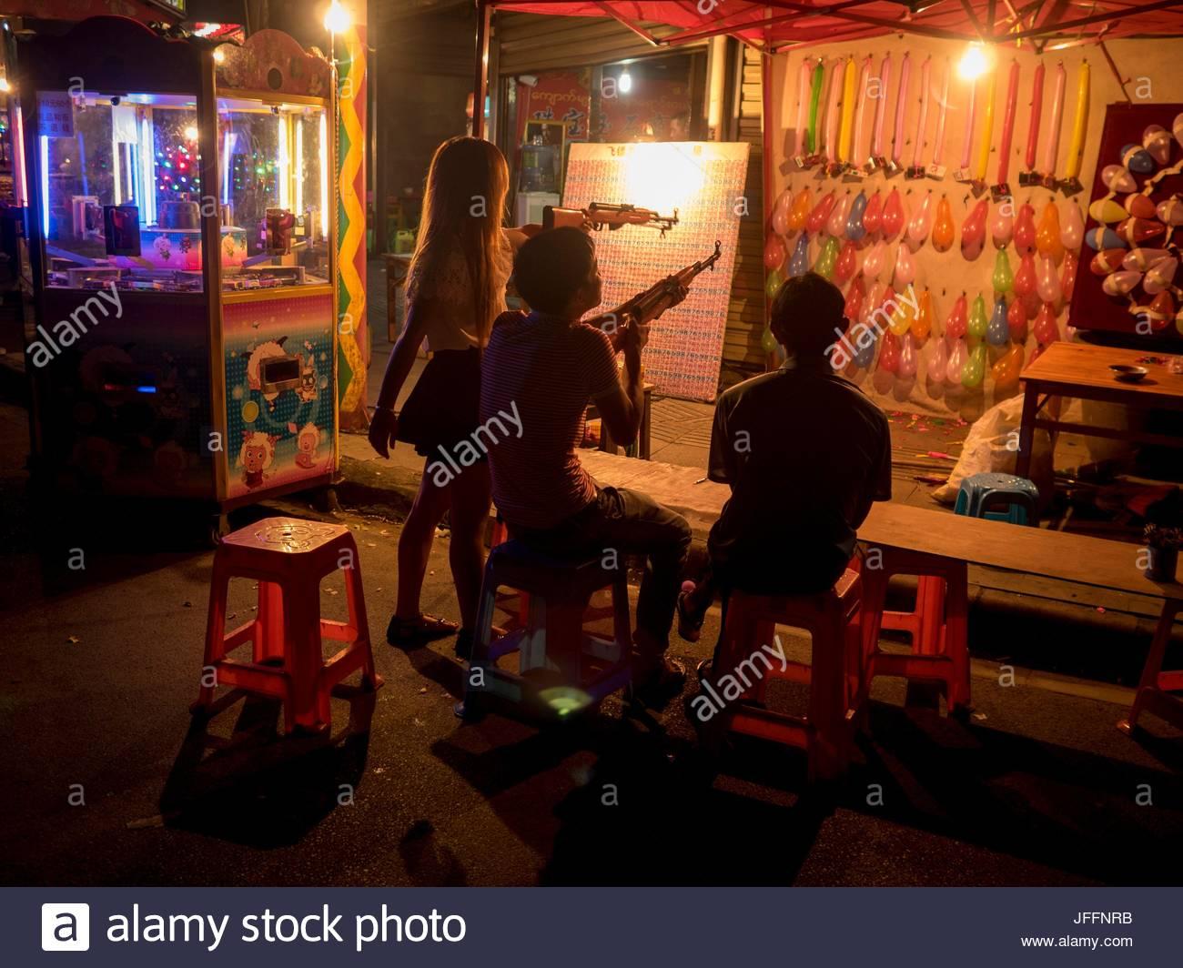 Los jóvenes en una feria de globos de disparo. Imagen De Stock