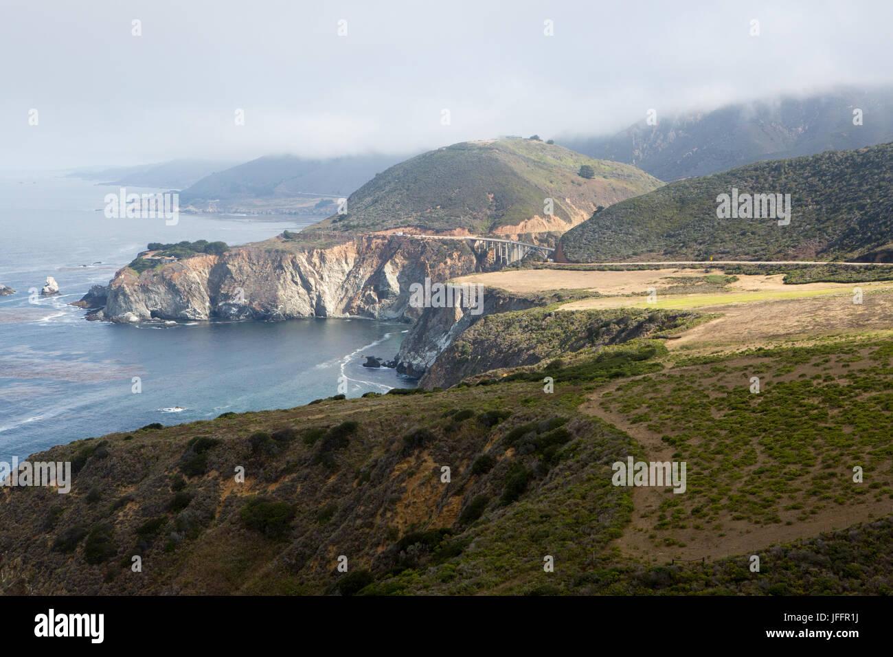Nubes sobre la costa de California, playas, formaciones rocosas y la Pacific Coast Highway, cerca de Bixby Puente. Imagen De Stock