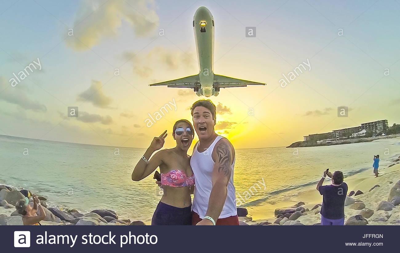 Una pareja de turistas con una GoPro para tomar un avión con un selfie acercándose. Imagen De Stock