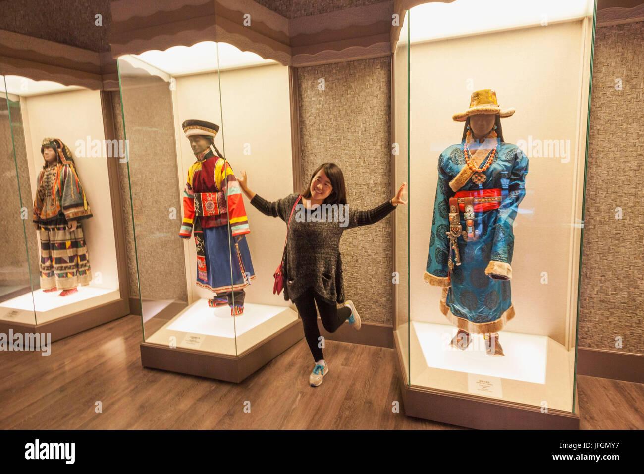 China, Shanghai, el museo de Shanghai, Niña posando con minorías étnicas exhibe ropa Imagen De Stock