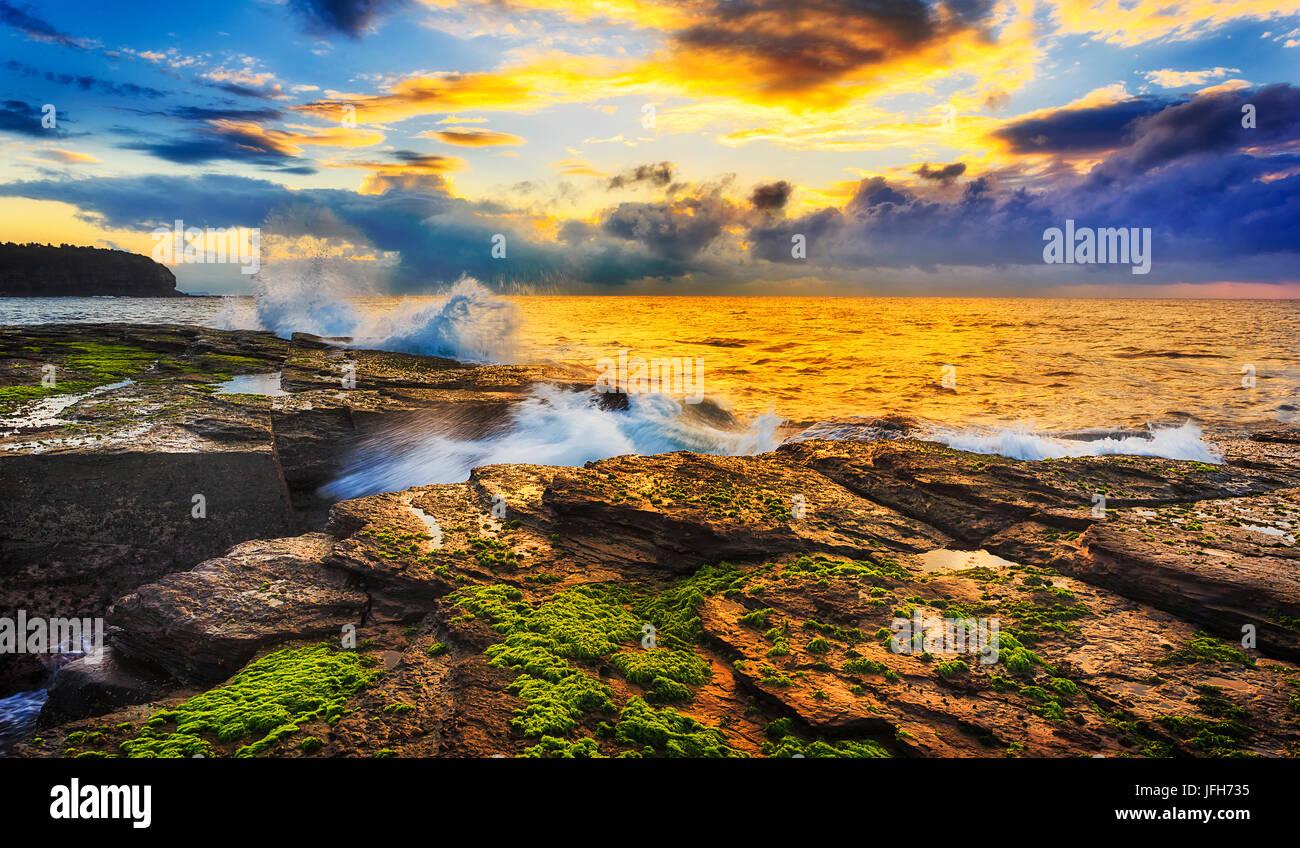 Colorido cálido sol arroja sobre las rocas de piedra arenisca y algas alrededor erosionado crack en Sunrise Imagen De Stock