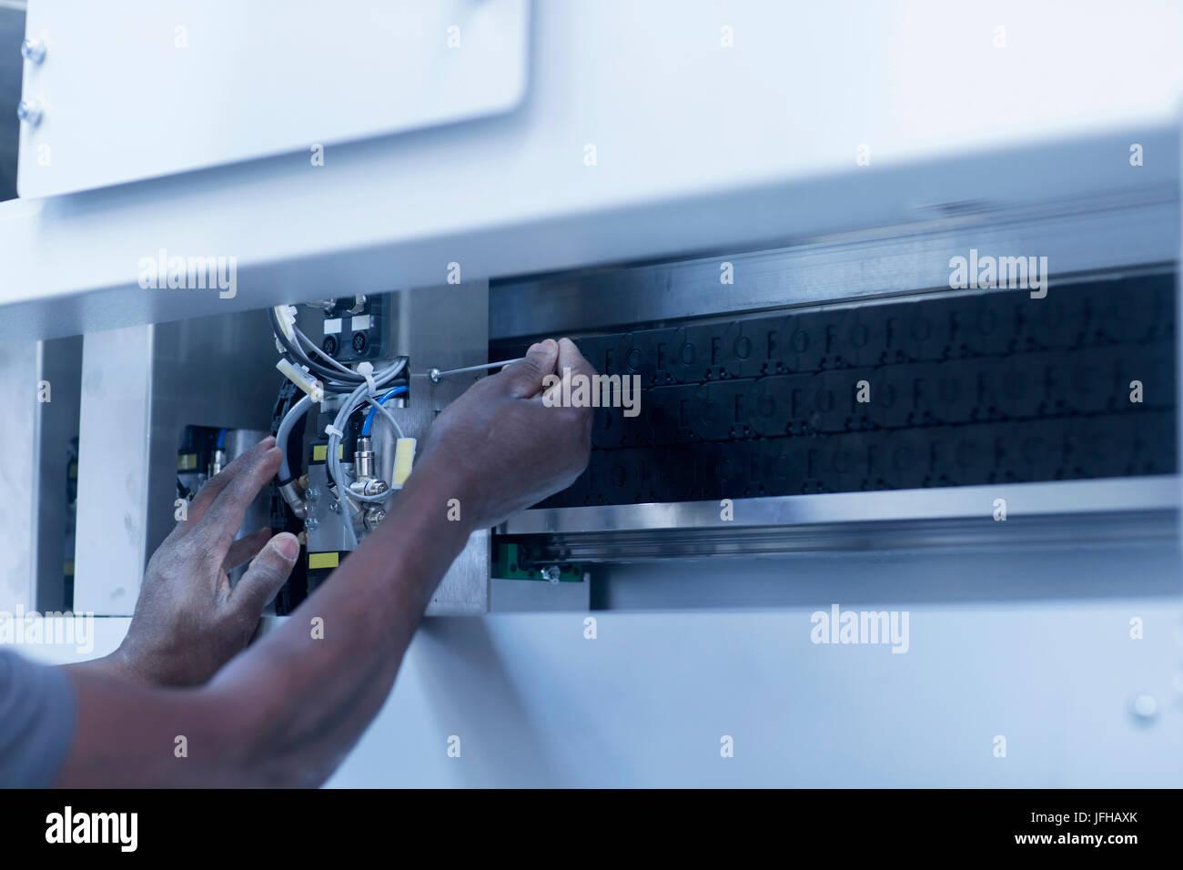 Parte media del ingeniero reparaciones a la máquina en la planta Imagen De Stock