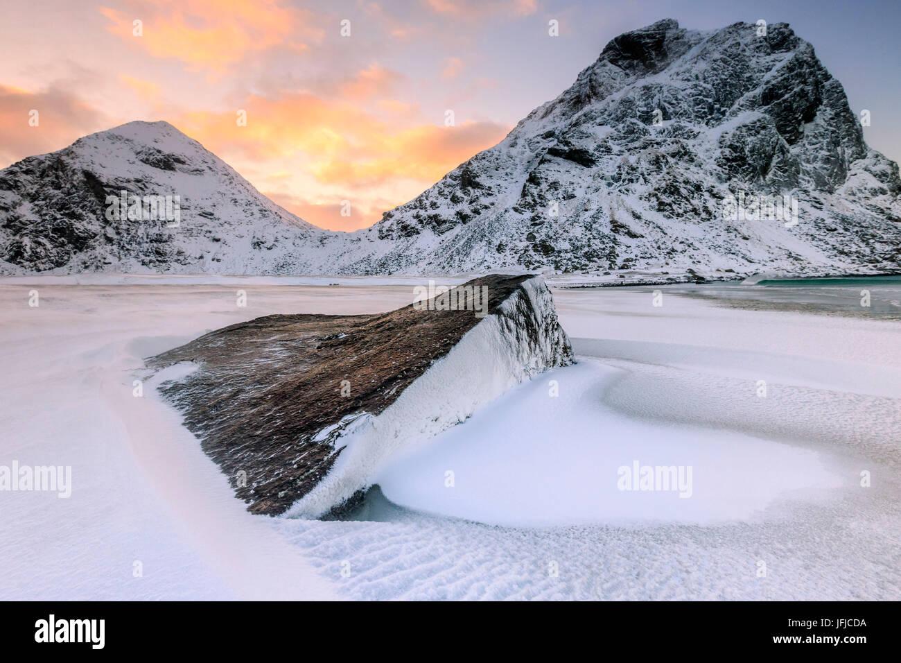 Amanecer ilumina las rocas modeladas por el viento rodeado de nieve fresca, Uttakleiv Islas Lofoten Noruega Europa Imagen De Stock