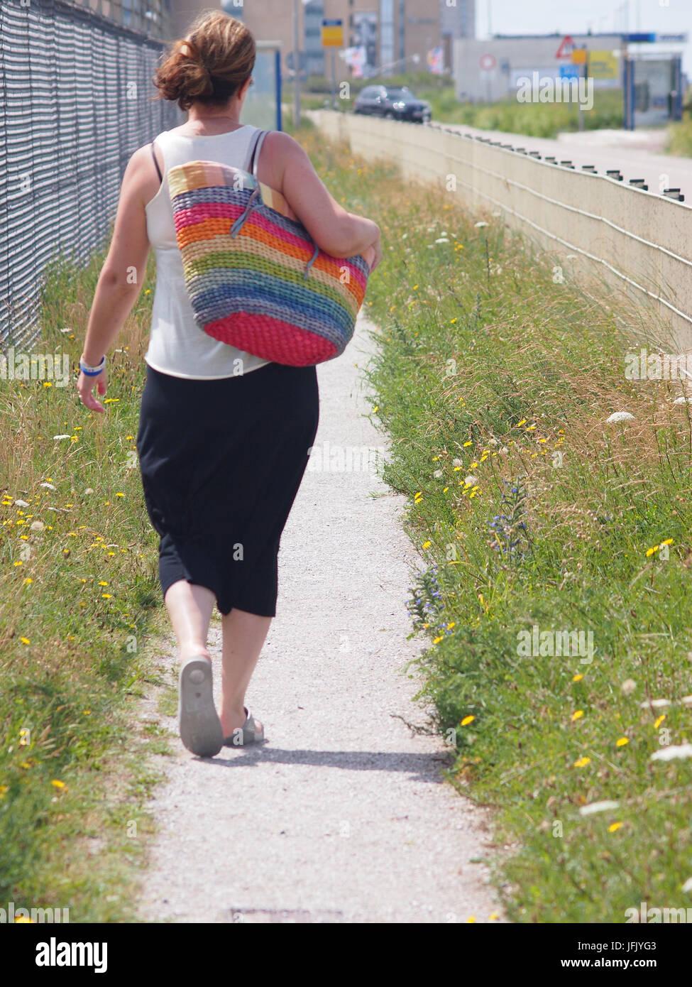 Mujer vistiendo una falda negra y top blanco caminando por un sendero costero con una gran stripey, colorista bolsa Imagen De Stock