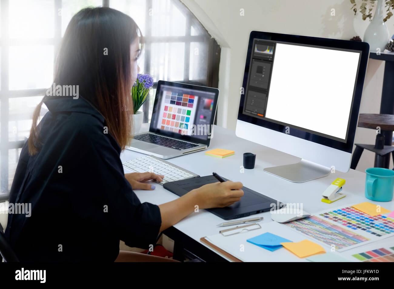 Joven fotógrafo y diseñador gráfico en el trabajo en la oficina. Monitor de pantalla en blanco para la visualización gráfica de montaje. Foto de stock