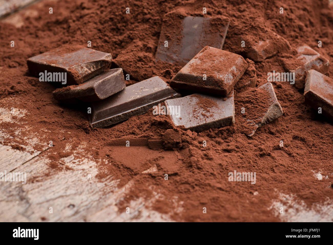 Montón de cacao en polvo con bloque de chocolate sobre la mesa de madera Imagen De Stock