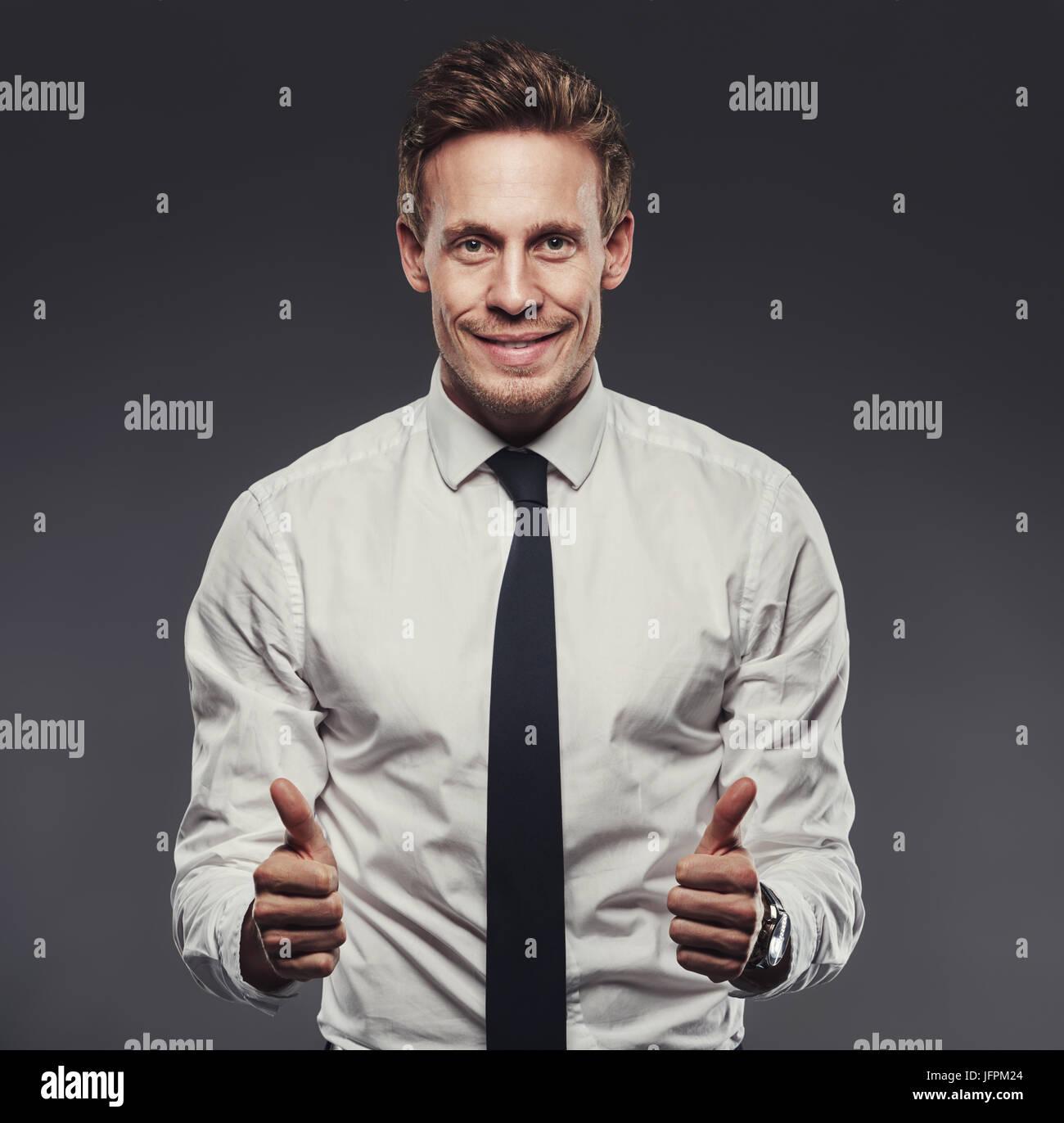 Sonriente joven empresario llevaba una camisa y corbata dando un entusiasta Thumbs up estando sola en un estudio Imagen De Stock