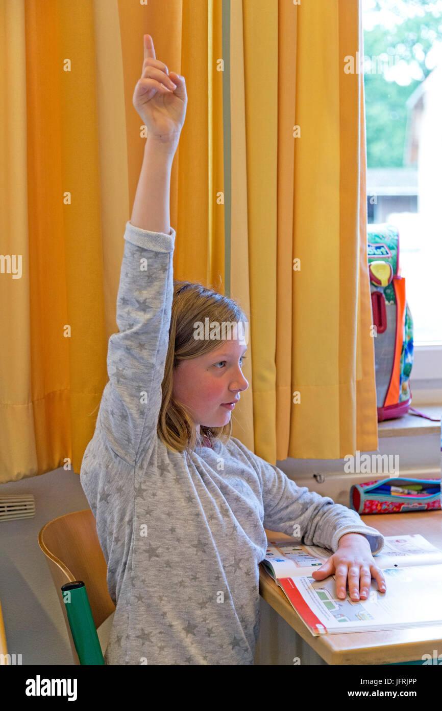 Niña en la escuela primaria levantando su mano Imagen De Stock