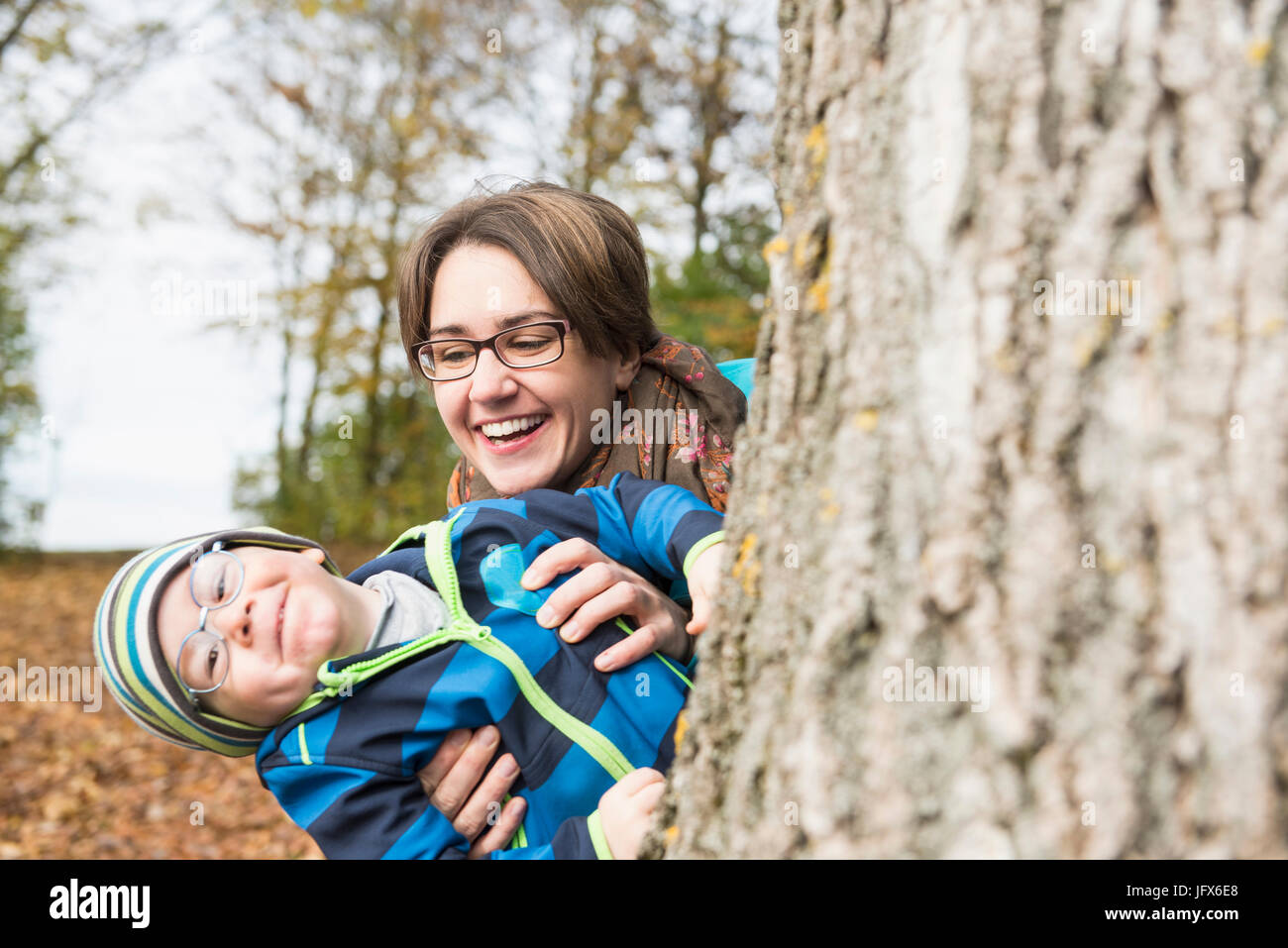 Madre e hijo peeking del gran árbol y riendo en el paisaje del otoño Foto de stock