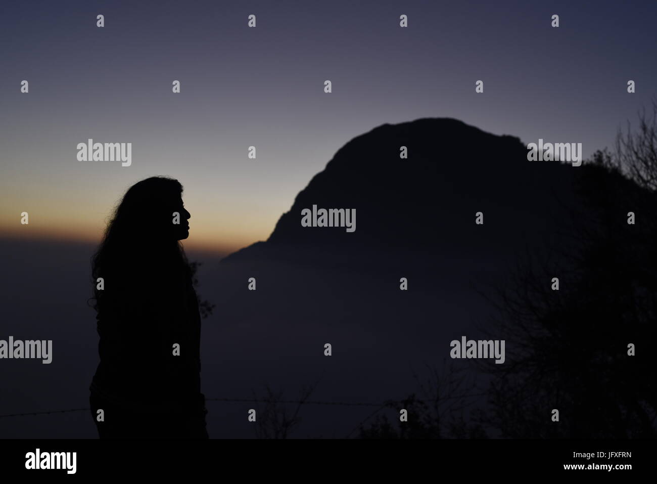 Scenic hermosa puesta de sol vista desde el punto más alto de la montaña naranja azul cielo en la oscuridad a Dhanaulti, Uttrakhand, India, Asia Foto de stock