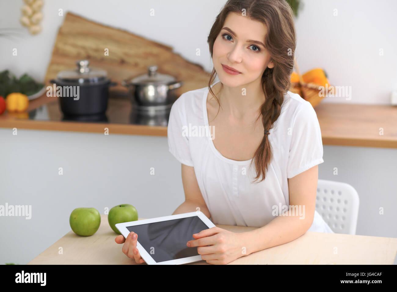 Mujer joven morenita es cocinar en la cocina. Ama de casa elige la mejor receta usando equipo de touchpad. Concepto Imagen De Stock