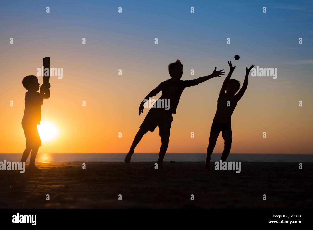 Niños jugando críquet en la playa cuando se pone el sol, Devon, Reino Unido Imagen De Stock