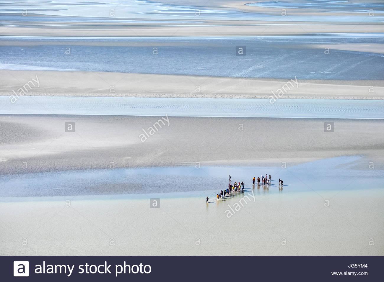 Francia, Normandía, Manche el departamento, Le Mont-Saint-Miichel. Hay turistas que caminan en las marismas cerca del Mont en marea baja. Foto de stock