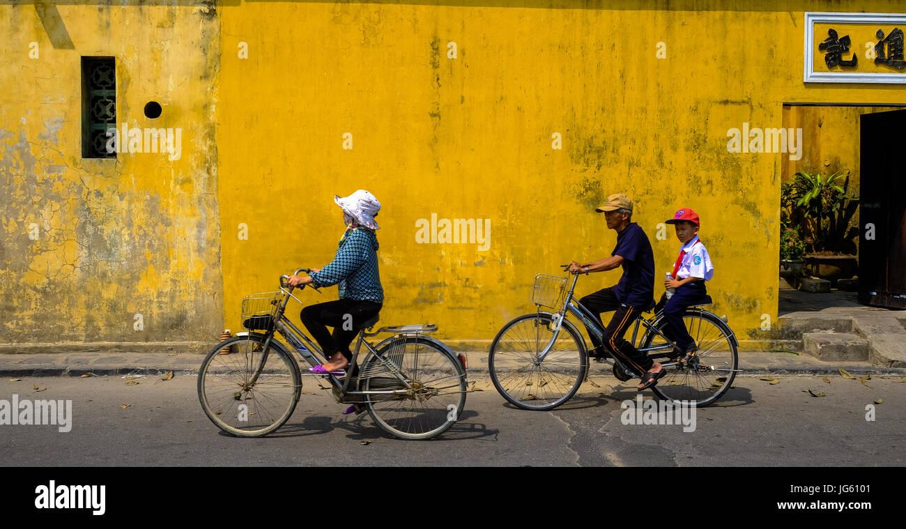 Una mujer vietnamita va en bicicleta en una calle de Hoi An, Vietnam Imagen De Stock