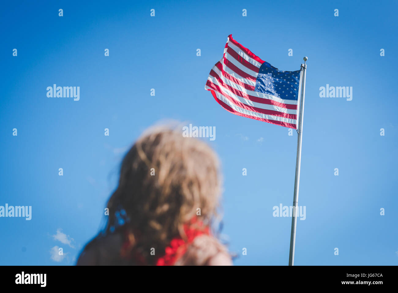 Una niña mira a la bandera americana. Imagen De Stock