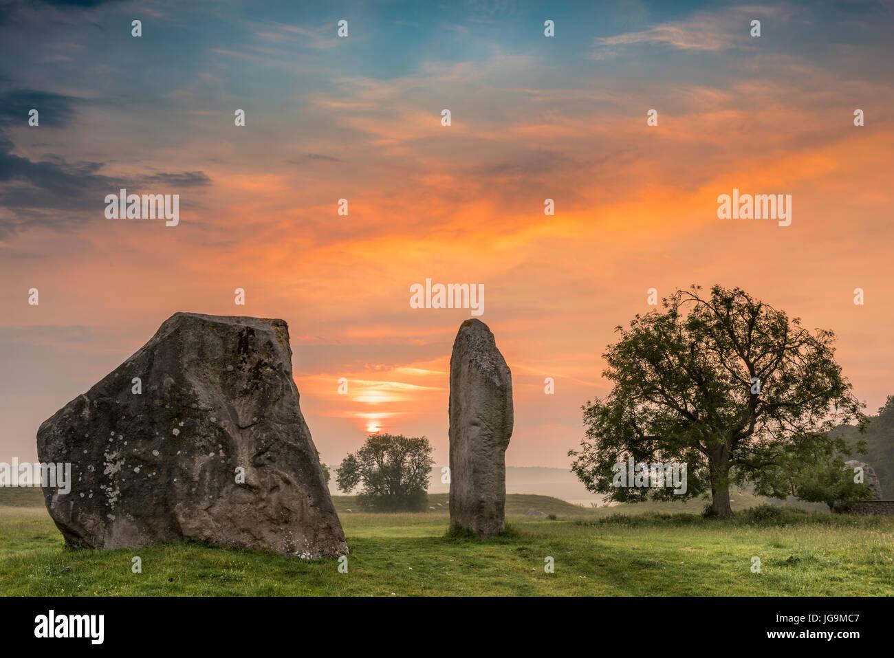 Las nubes parte al amanecer sobre las antiguas piedras Sarsen Avebury en Wiltshire en la víspera del solsticio de Foto de stock