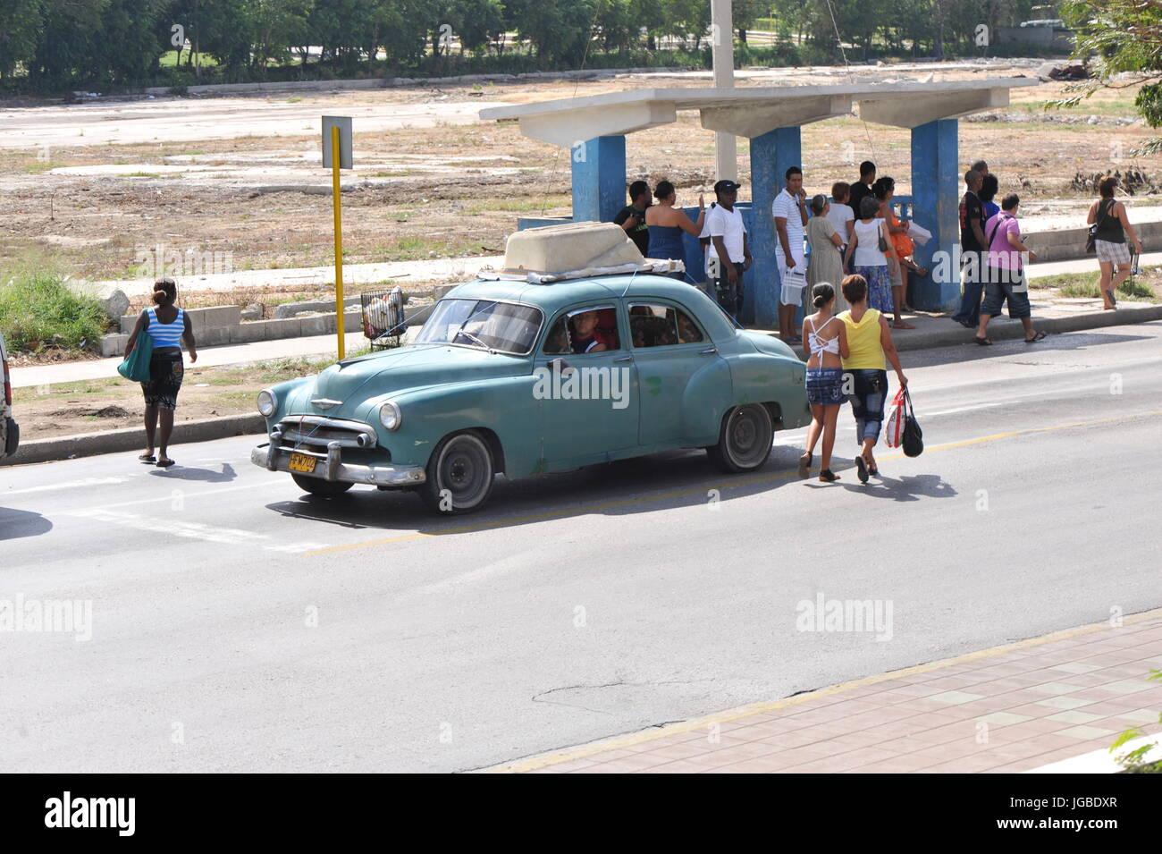 Los cubanos local espere en la parada del autobús para ir a trabajar como azul clásico americano por unidades Imagen De Stock