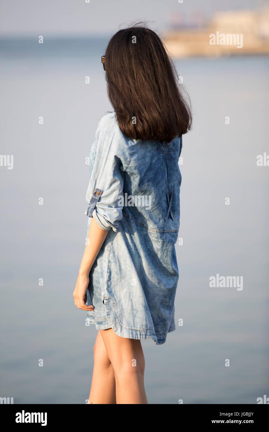 Vista trasera de una mujer joven llevaba un vestido de verano azul por el mar permanente Foto de stock