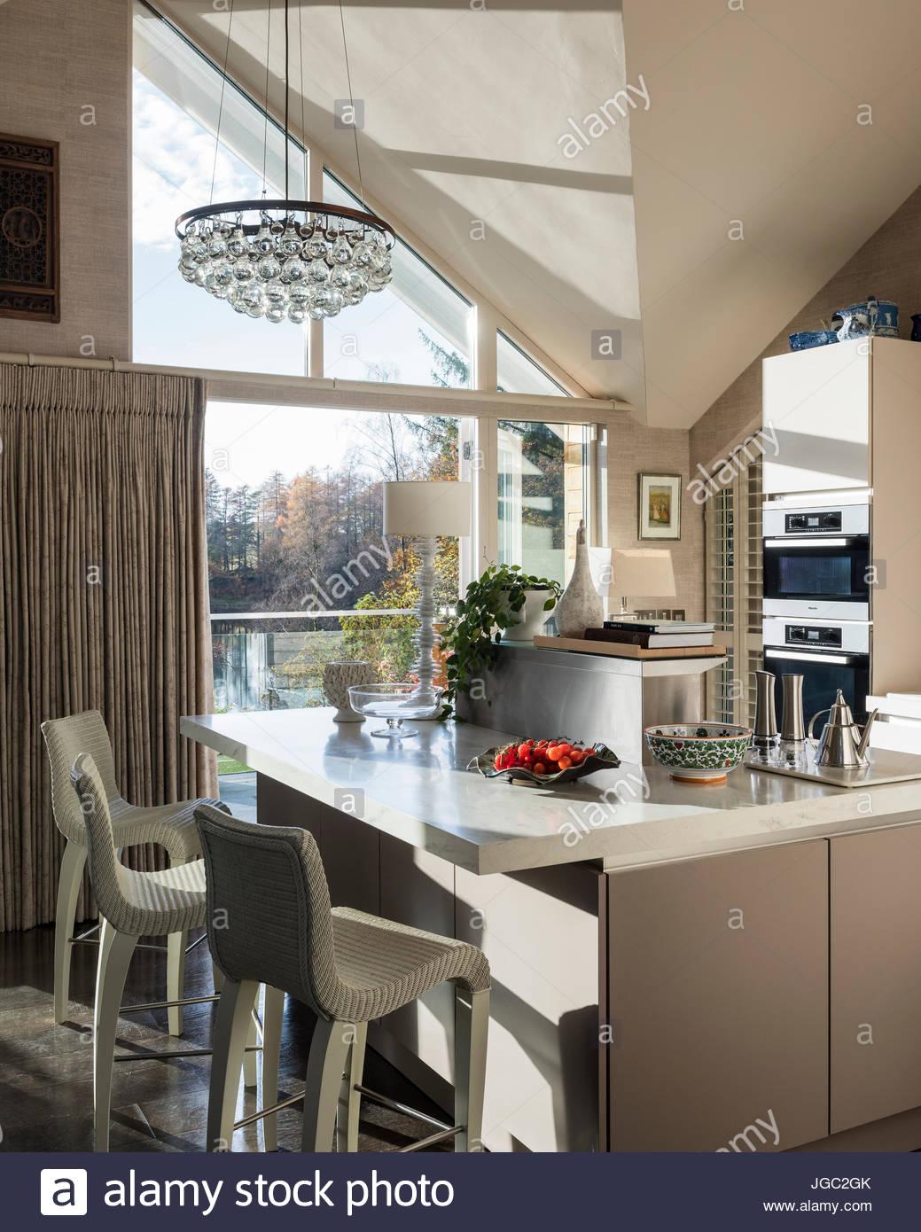 Colgante bombilla encima de barra de desayuno en un bastidor en cocina con vista al lago Imagen De Stock