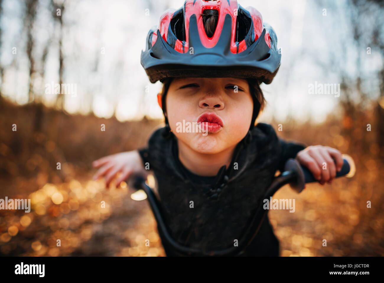 Chico en una bicicleta con un casco fruncir los labios Foto de stock