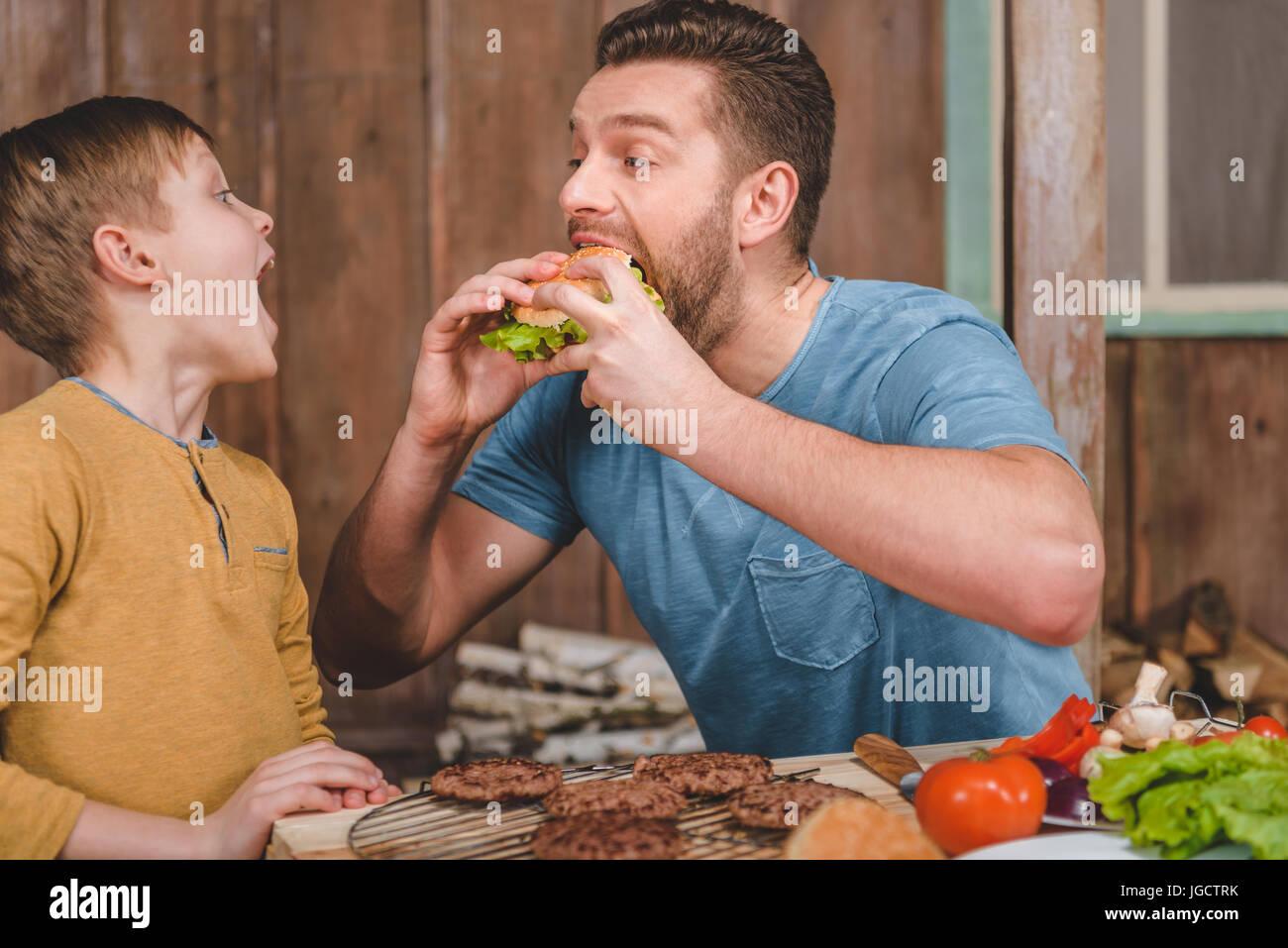 Vista lateral del hombre comiendo hamburguesas caseras con pequeño hijo cerca Imagen De Stock