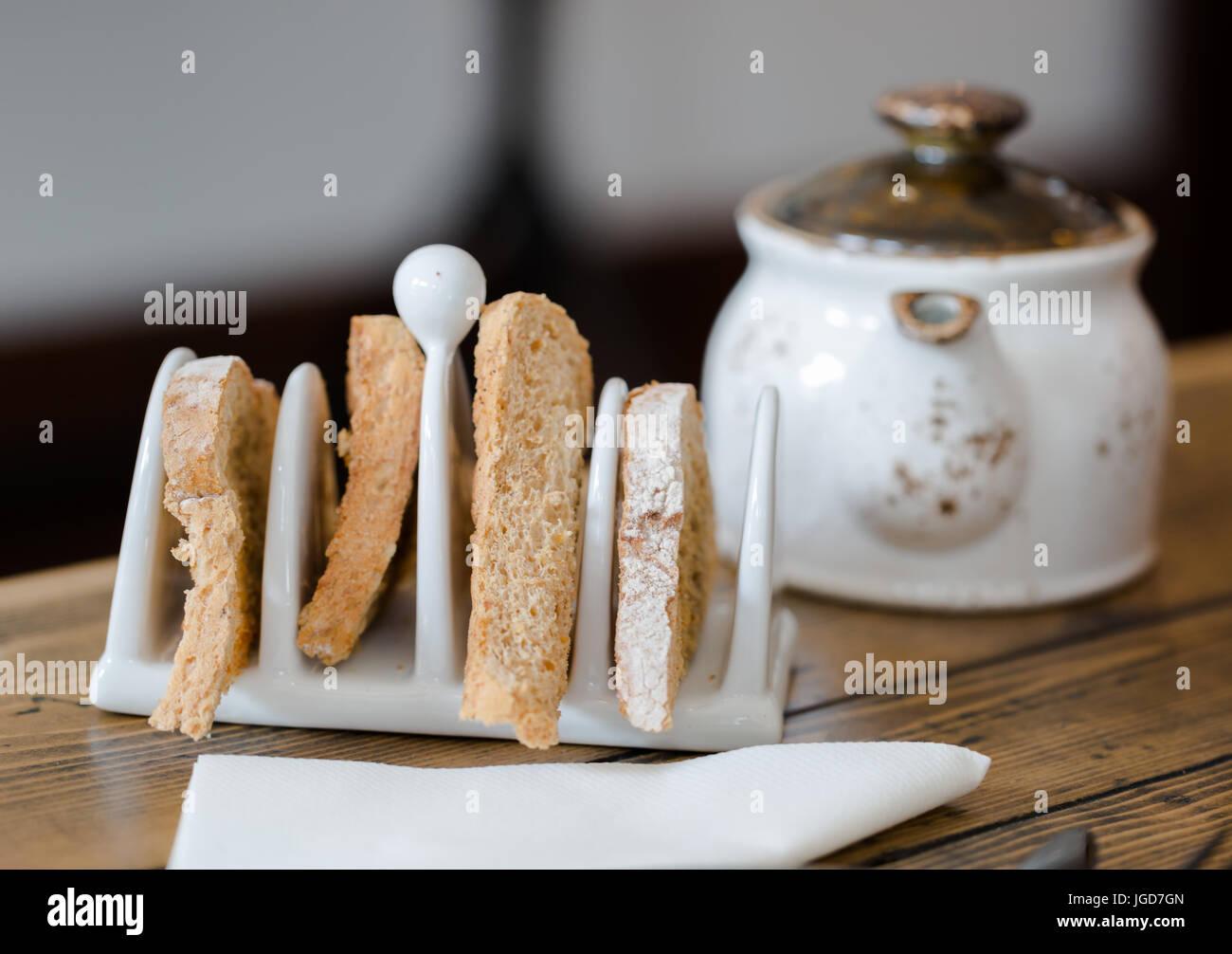 Cuatro rebanadas de pan tostado en tostadas de soporte en la mesa de madera de cerca. Enfoque en primer plano, tetera en el fondo borroso. Vista cercana de ángulo bajo. Shal Foto de stock
