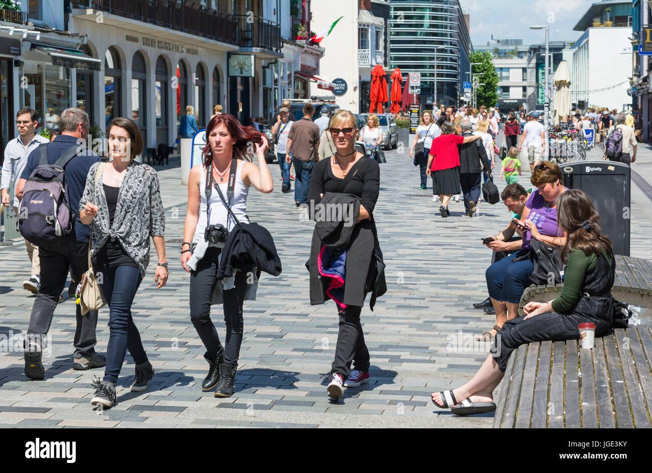 Las hembras jóvenes amigos y otras personas caminando en una única zona peatonal en el Reino Unido. Imagen De Stock