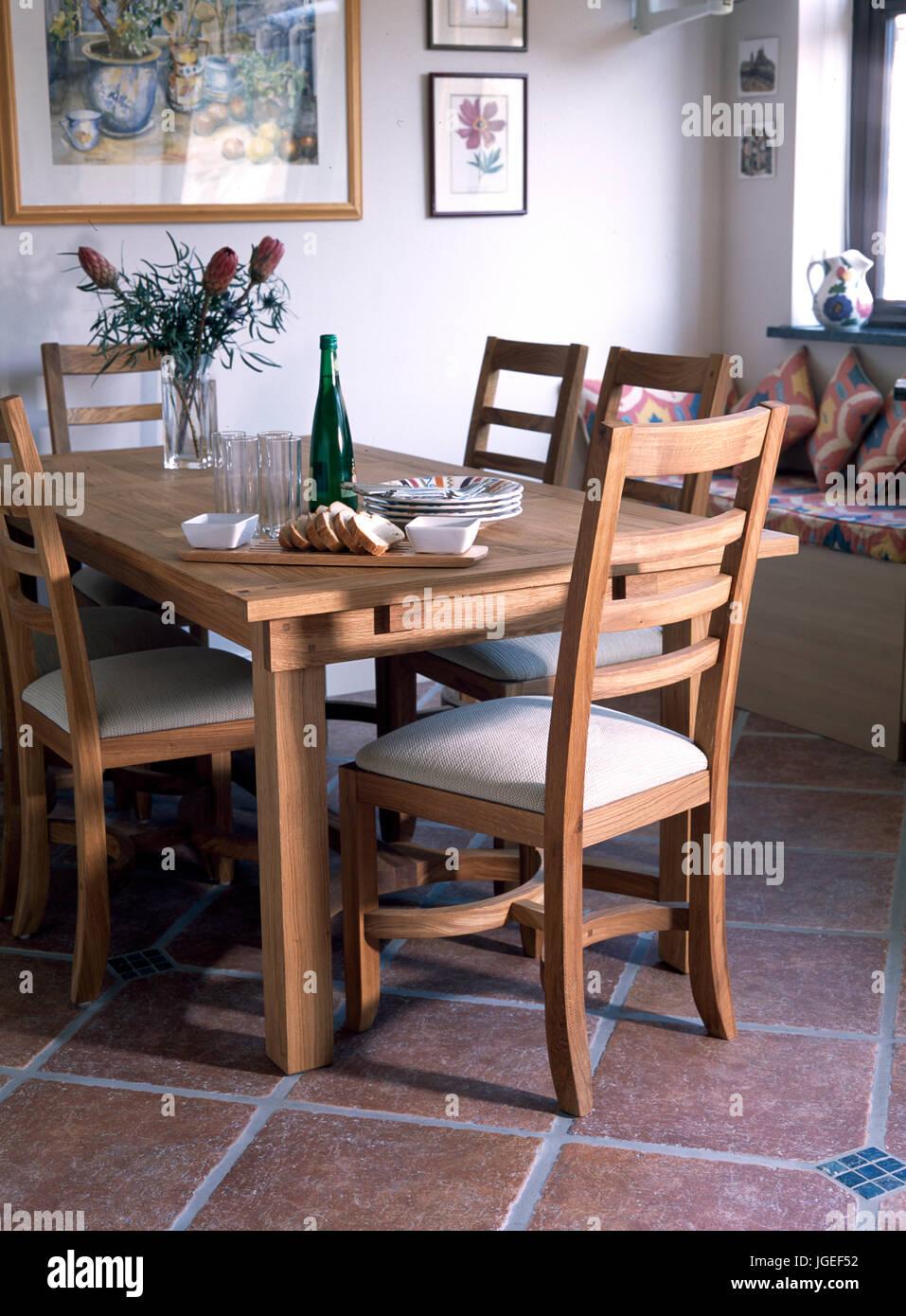 Mesa y sillas de comedor de madera en el suelo de baldosas de terracota.  Imagen f4269bd47a2f