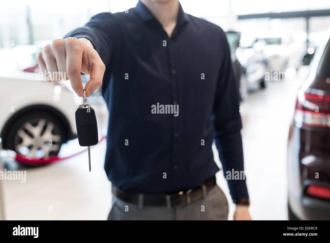 Parte media de vendedor mostrando las llaves del coche Imagen De Stock
